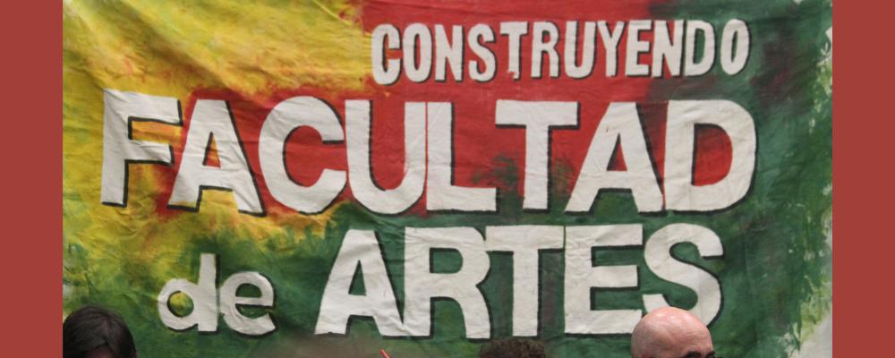 """Imagen de fotografía de la sesión del CDC con banera del gremio estudiantil que lleva el siguiente texto: """"Construyendo Facultad de Artes"""""""